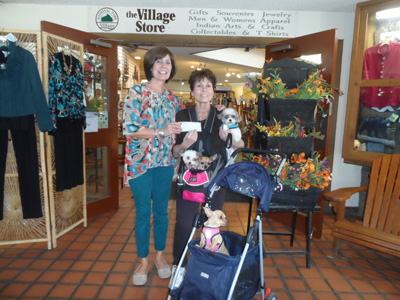 Katie Webermeier of the Village Store presents a check for $1,000 to Estes Park Pet Association president Carolyn Fairbanks (and friends) on behalf of the Rocky Card.
